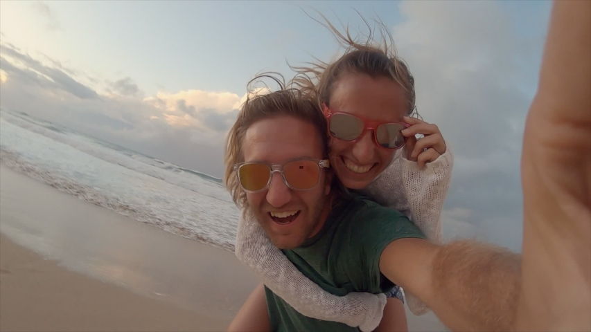 Couple taking cool selfies on the beach piggy back. Young people travelling taking selfies. Slow motion  | Shutterstock HD Video #1043624359