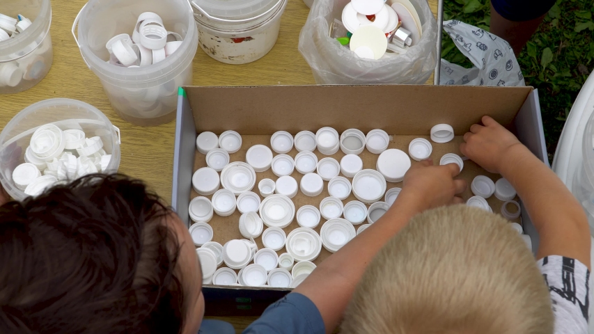 Novosibirsk, Russia - 25 July 2019 - AAdults and children sort white caps of plastic bottles by different kinds of PET plastic. Teaching children to protect the environment, help nature. 4k footage.