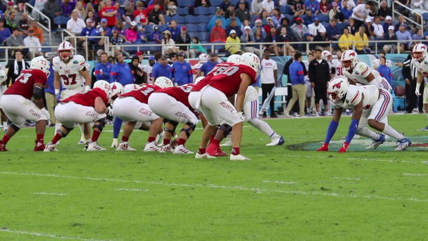 Boca Raton, Florida/USA - December 21, 2019: Florida Atlantic Owls vs SMU Mustangs. Cheribundi Boca Raton Bowl 2019. College Football players on the field in attack. Football footage with sound.
