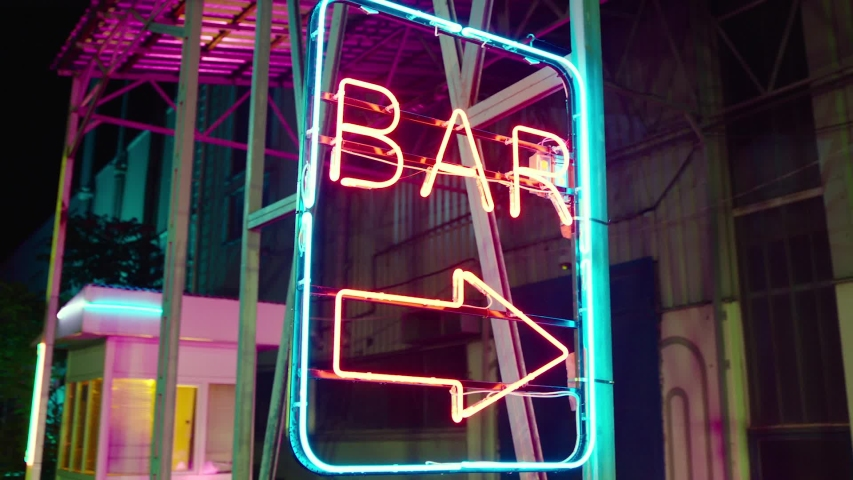 Neon bar sign medium shot . Night exterior video footage of vintage neon sign. A nighttime exterior shot of a generic, unbranded bar and restaurant in street . Gimbal shot .