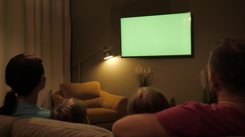 Rear View Of Family With Children Sitting On Sofa In Living Room Evening Watching Green Mock-up Screen TV Together. Family Sitting Together Sofa In Their Living Room Night Watching TV Green Screen. #1043677150