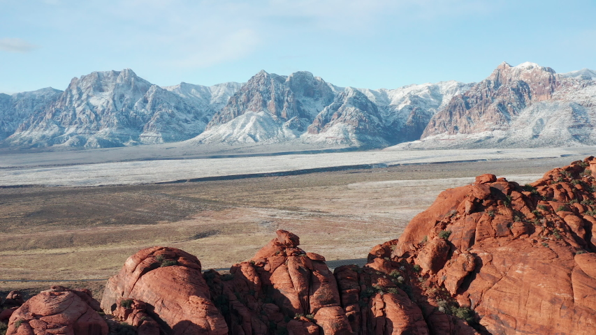 Aerial scenic shot of snow covered Red Rock Canyon mountains, sandstone cliffs | Shutterstock HD Video #1043706721