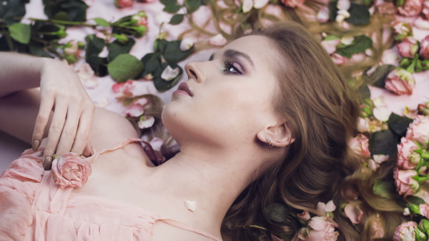 Beautiful girl lies in roses. Delicate scarlet roses and a woman. Aromatherapy. Valentine's Day. Natural cosmetic. Gentle perfume.