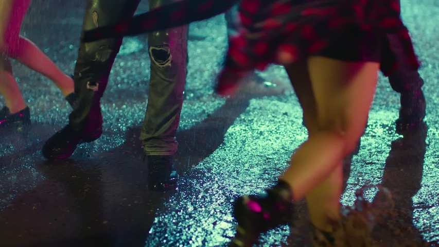 Footage of young people's feet and legs jumping and dancing in the rain at night.