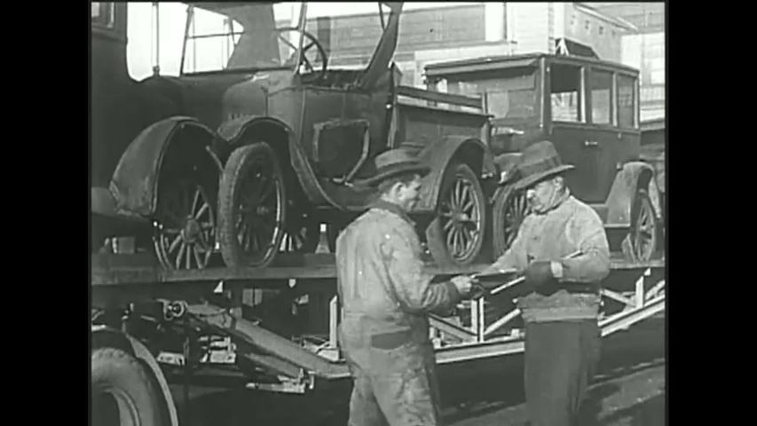 CIRCA 1920s - Henry Ford sits on the assembly line in the last Model T and Model T automobiles are scraped.