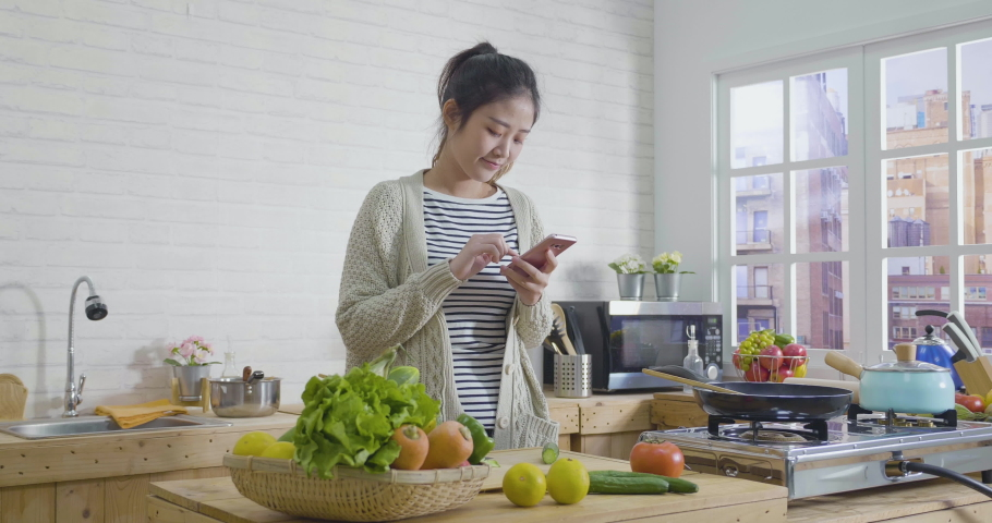 Cheerful happy asian chinese woman dancing in wooden kitchen interior while surfing social media on smartphone at home in the morning. young girl checking recipe on mobile phone with fresh vegetables | Shutterstock HD Video #1043765251