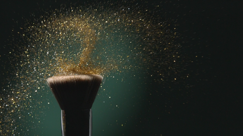 Glitter on a Make-up Brush Flying Away with Woman Finger Flicking Shot in Slow Motion on Green Aqua Menthe Color Background Royalty-Free Stock Footage #1043766691