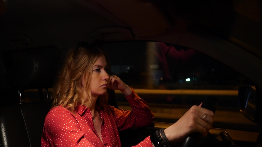 A young girl is tired and falls asleep at the wheel of a car. It is dangerous to fall asleep driving a car on a night road. A woman in red dress closes her eyes while driving.