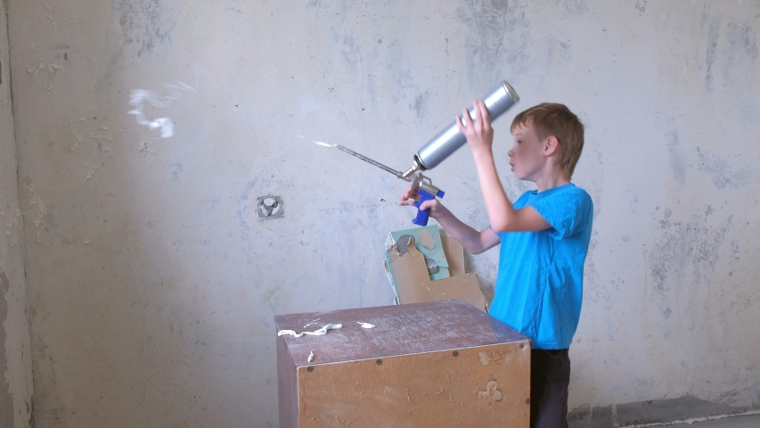 Boy is playing with mounting foam while parents don't see him. Renovation and construction at home. He applying construction foam in room around himself on wall and floor.