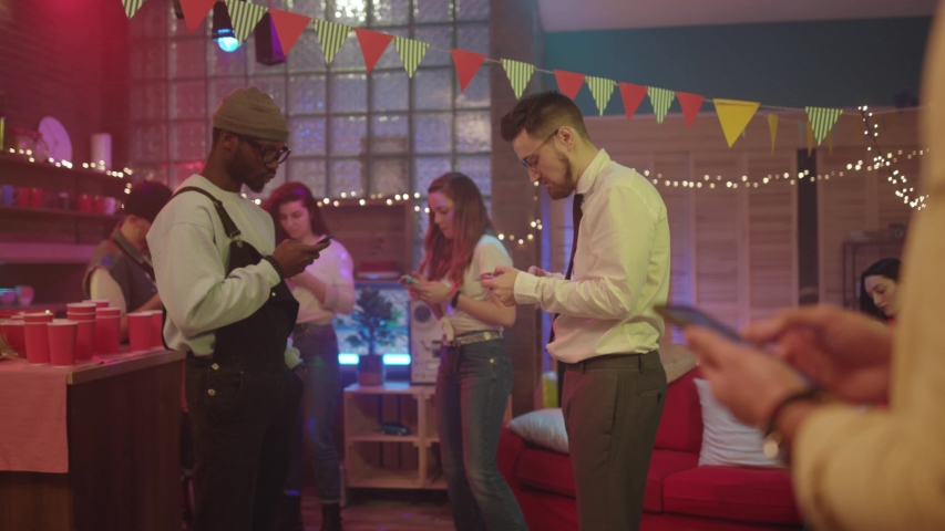 Glamorous interracial young people using smartphones socializing checking internet instead of dancing. Boring party. Wireless communication. Royalty-Free Stock Footage #1043826493