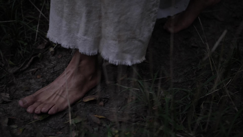 Closeup of robed mans feet or Jesus walking through forest trees. Dramatic and moody. Slow motion.