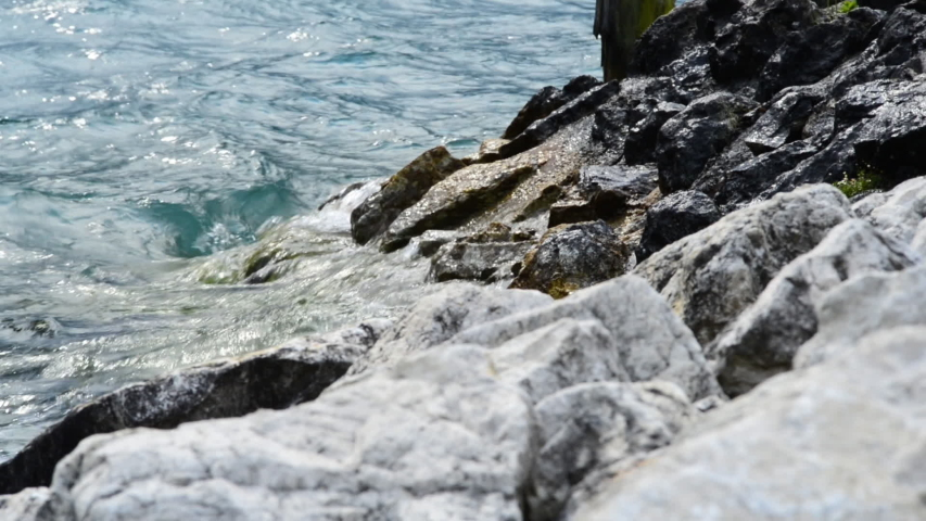 The waves breaking on a stony beach, forming a spray  | Shutterstock HD Video #1043832838