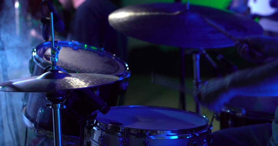A drummer plays on a dark stage in the fog and light of lanterns, in soundcheck time. The average plan is a hand with a stick, percussion, cymbals, a snare drum. | Shutterstock HD Video #1043834455