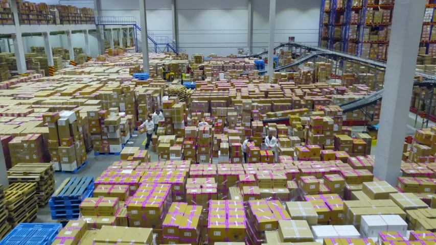 Warehouse with workers, cardboard boxes inside on pallets racks, logistic center | Shutterstock HD Video #1043852224