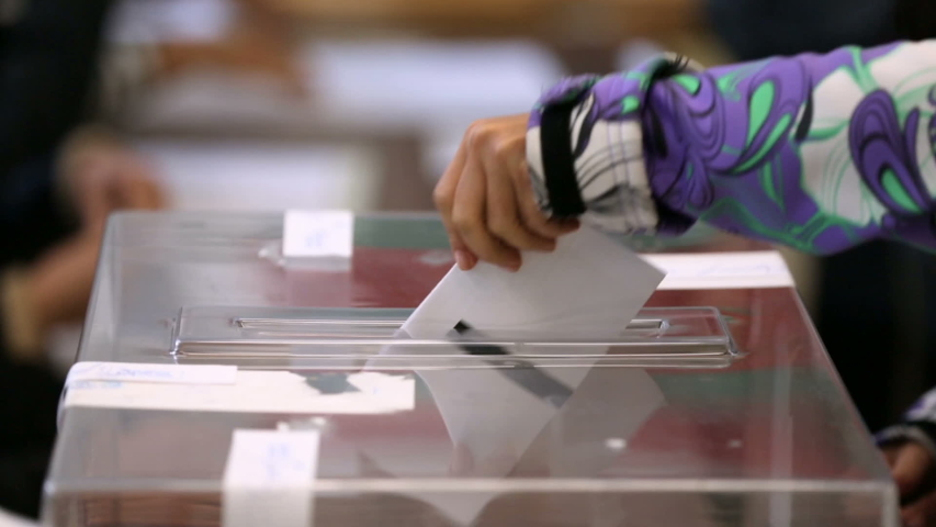 A woman casts her envelope vote into a transparent plastic ballot box. Human hand voting.