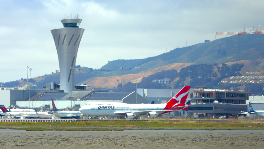 SAN FRANCISCO, CA - 2020: Qantas Boeing 747-400 Jet Airliner Taxiing Past ATC Air Traffic Control Tower Arriving at San Francisco SFO International Airport on a Sunny Day in California