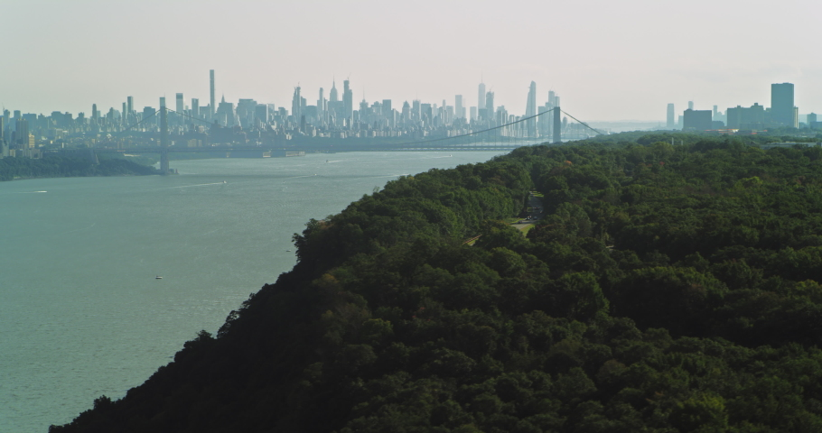 Aerial view of lush green forest on island with Manhattan skyline in the background in New York during the day under overcast blue sky. Wide shot on 4K RED camera.