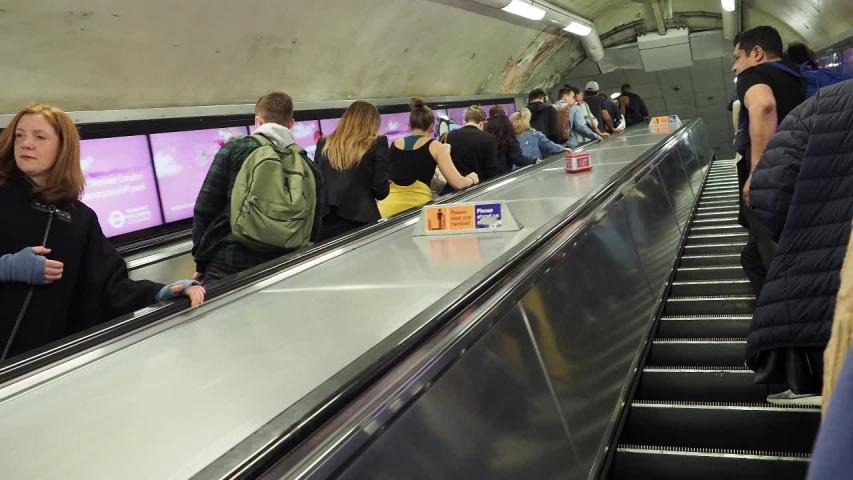 LONDON, UK - CIRCA SEPTEMBER 2019: Travellers on London Underground Tube station escalator