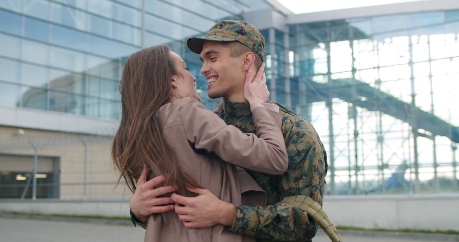 Excited soldier coming back from military service welcomed by his wife. Happy girl greeting and hugging her boyfriend in military uniform. Concept of happy reunion and military service