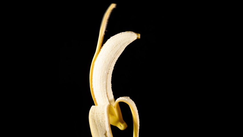 Banana being peeled with no hands on black background | Shutterstock HD Video #1043936410