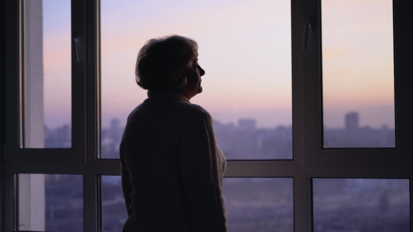 Lonely senior woman sadly looking in window, missing family at retirement home