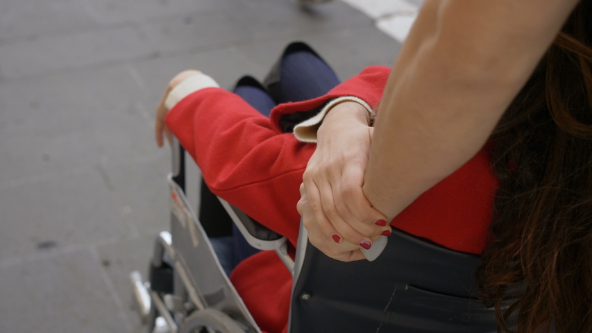 young brunette woman holding her boyfriend' s hand pushing her wheelchair Royalty-Free Stock Footage #1043947144