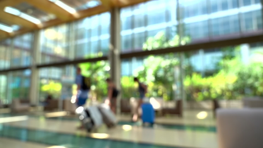 Blurry defocused corridor of hall of modern hotel resort. Blurry anonymous people walking with luggage and other people taking videos of their trip. Full hd video footage. Royalty-Free Stock Footage #1043957809