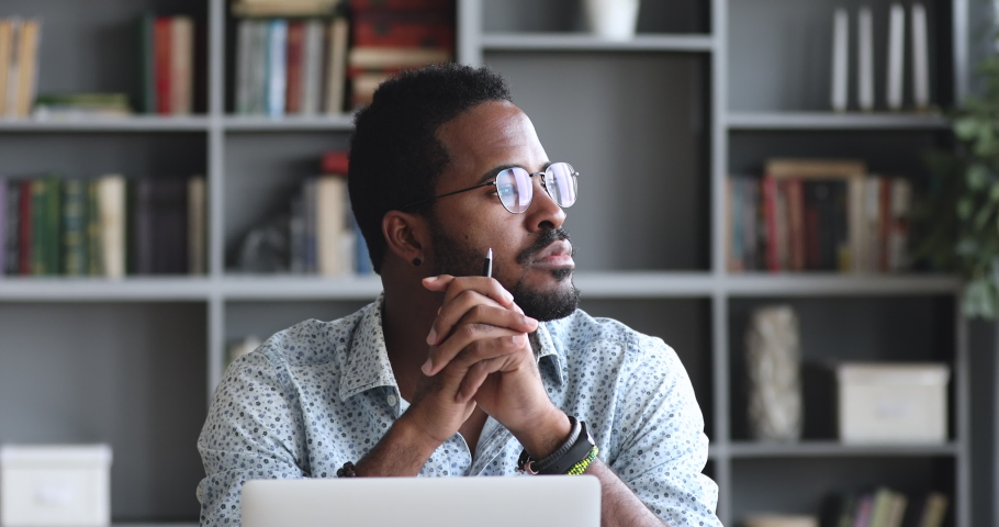 Thoughtful serious young african american man student writer sit at home office desk with laptop thinking of inspiration search problem solution ideas lost in thoughts concept dreaming looking away