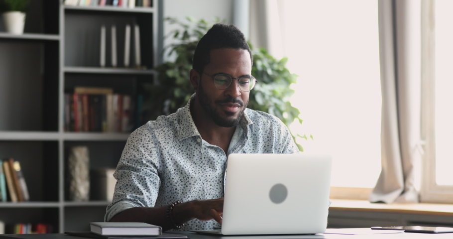 Focused african american business man student entrepreneur typing on pc study online course with laptop, serious young mixed race guy work distantly from home office using computer device sit at desk Royalty-Free Stock Footage #1043980033