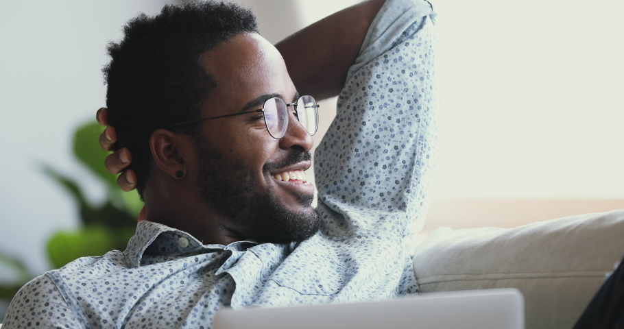 Happy afro american man wear glasses relax with laptop looking away dreaming resting on sofa at home, smiling young mixed race guy lounge on couch with notebook feel satisfied concept, close up view | Shutterstock HD Video #1043980060