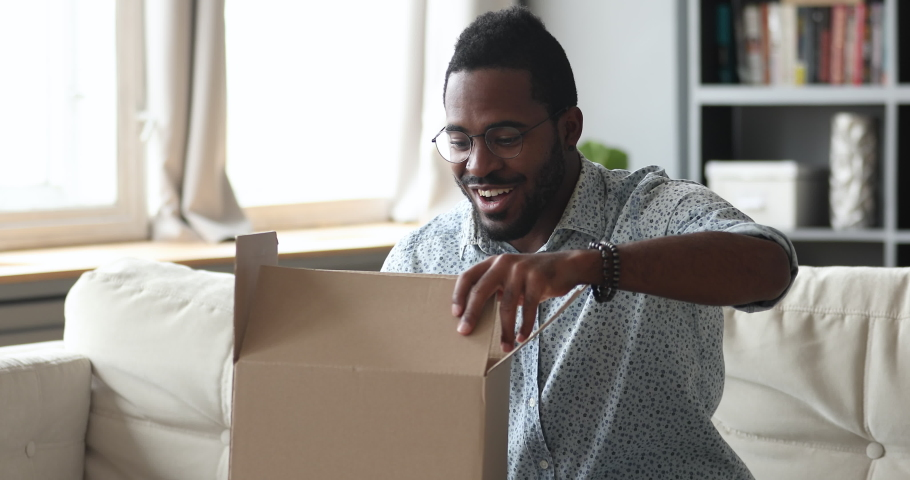 Happy african man customer open cardboard box receive gift online purchase in postal parcel shipping delivery service concept, satisfied mixed race male consumer unpacking package sit on sofa at home