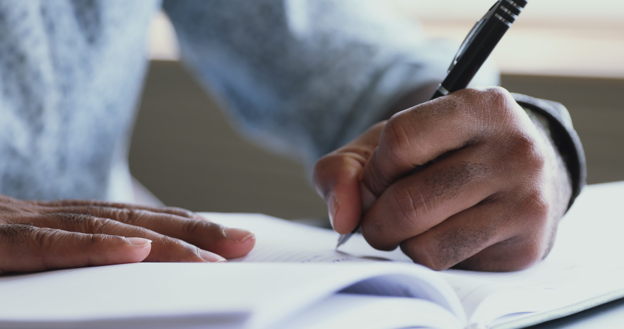 African american left-handed businessman holding pen writing new appointments information in organizer concept, mixed race male hands making notes in personal paper planner at desk, close up view