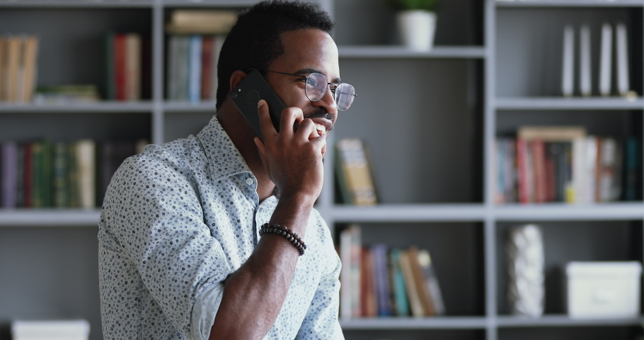 Happy millennial hipster african american businessman stand in modern office talk on phone, smiling young mixed race entrepreneur speak on cellphone, mobile tech professional communication concept