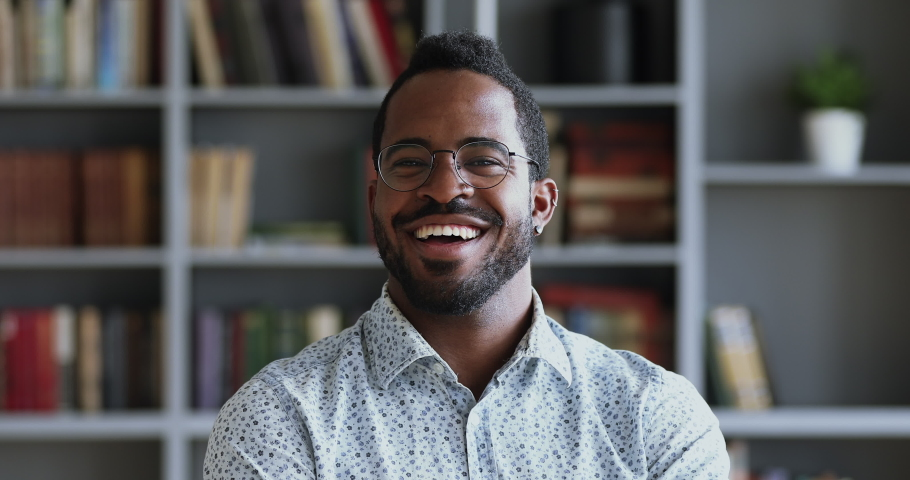 Happy african young adult businessman wear optical glasses dental smile look at camera in home office, mixed race student professional teacher posing on bookshelves background, close up portrait Royalty-Free Stock Footage #1043980162