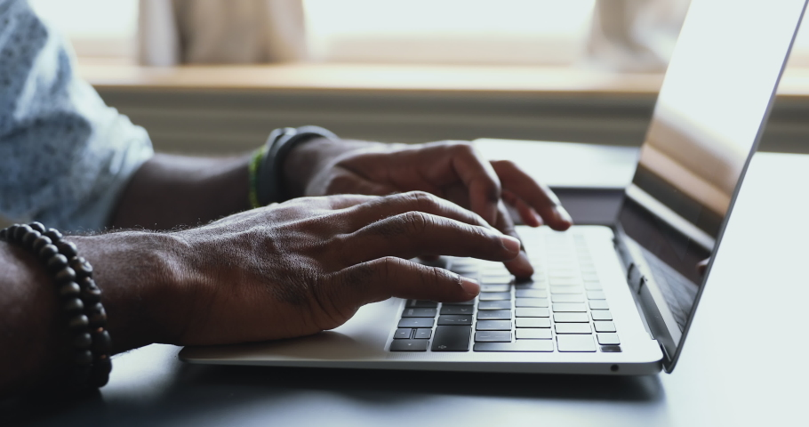Male african american user hands typing on laptop keyboard sit at table, mixed race ethnic businessman hipster student professional study work with pc software technology concept, close up view | Shutterstock HD Video #1043980198