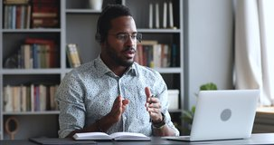 Serious young african businessman wear headset conference calling by webcam, focused mix race student study with online teacher in video chat look at laptop talk during videoconference at home office