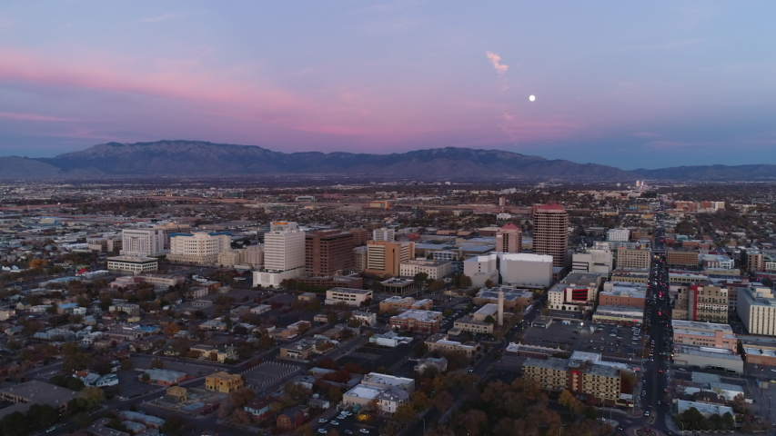 A low altitude aerial view of downtown Albuquerque and the Sandia Mountains at Dusk as the moon rises.