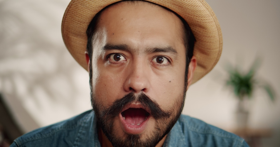 Close up of super surprised emotional Hispanic male with mustache and beard indoor in hat, cheerful brunette guy smiling of unexpected news showing expressive facial expression dressed in jeans shirt | Shutterstock HD Video #1043987641