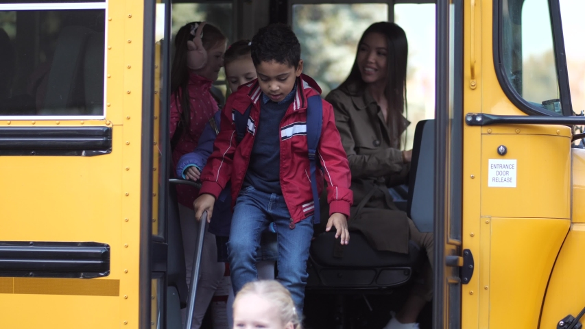 Smiling mixed race female driver of school bus waving goodbye to elementary age kids going to school. Diverse schoolboys and schoolgirls taking turns leaving yellow bus arriving to school Royalty-Free Stock Footage #1043996629