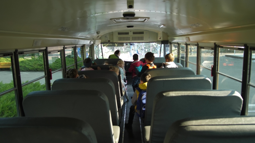 Back view of elementary age schoolchildren rising from seats to get off school bus. Mixed race woman driver waving goodbye to diverse preadolescent kids leaving school bus and going to school Royalty-Free Stock Footage #1043996665