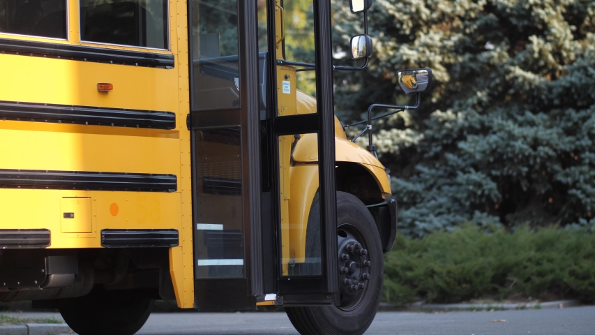 Cute schoolkids running in crowd to school bus standing with open doors near school. Happy elementary age children rushing home after lessons and pushing while getting on school bus waiting for them Royalty-Free Stock Footage #1043996671