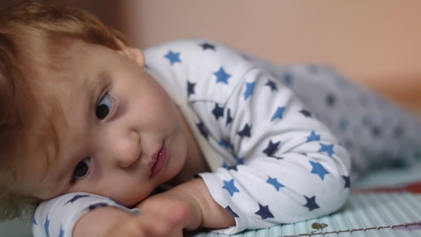 Portrait of a baby with cerebral palsy lying on his belly and playing at home. Special needs child. Handicapped baby boy close-up. | Shutterstock HD Video #1044000127
