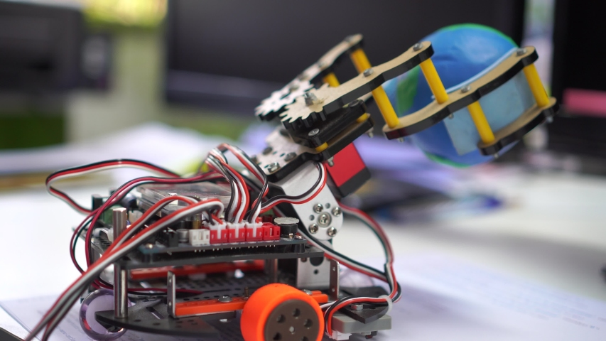Robotics technology, STEM education lab concept : Metal robot and electronic board robots holding model globe, Programs for learning coding study in computer laboratory in school on computer desk Royalty-Free Stock Footage #1044001099