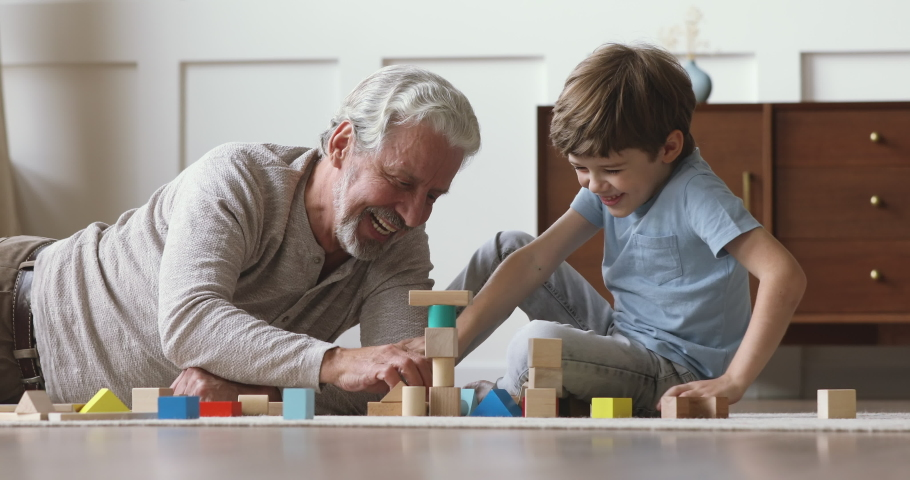 Happy old senior grandfather teach little grandson playing with wooden blocks on floor, carefree two generation family grandparent and cute small grandchild having fun building tower laughing at home