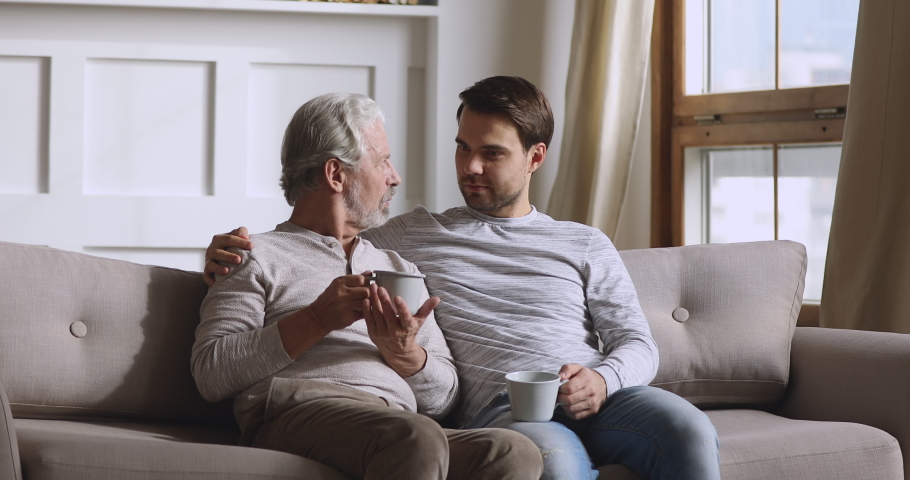 Serious happy two generation men family hold drinks having trust honest conversation chatting sit on sofa at home, senior old parent father talking to young adult grown son share news relax on couch