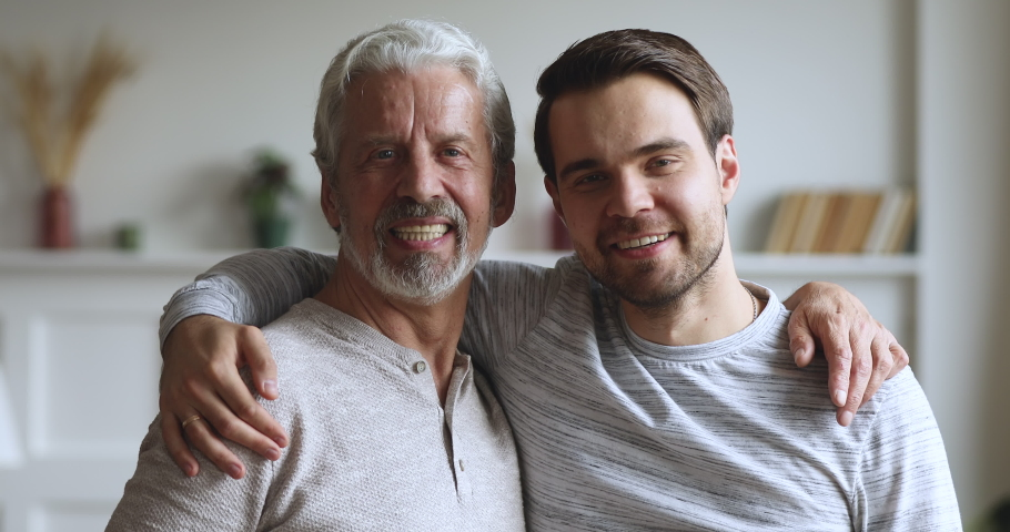 Happy handsome two age generations men family posing for portrait at home, smiling young adult son hugging senior older grey haired father embracing together looking at camera, close up portrait