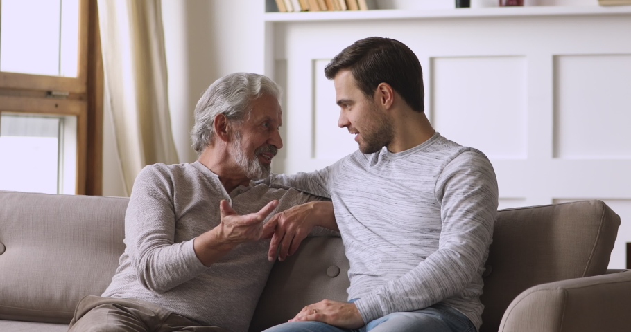 Friendly honest old father and young son talking on sofa, happy two generations male family having trust conversation chatting relaxing on couch in living room enjoy understanding and support concept