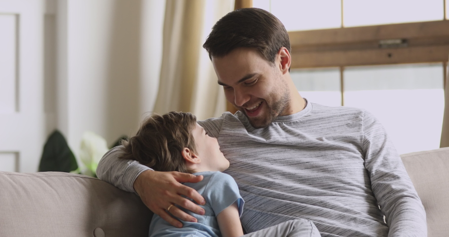 Caring happy young adult dad embracing small preschool child son having trust conversation cuddling sit on sofa, loving father enjoy talking with little kid boy enjoy honest communication concept