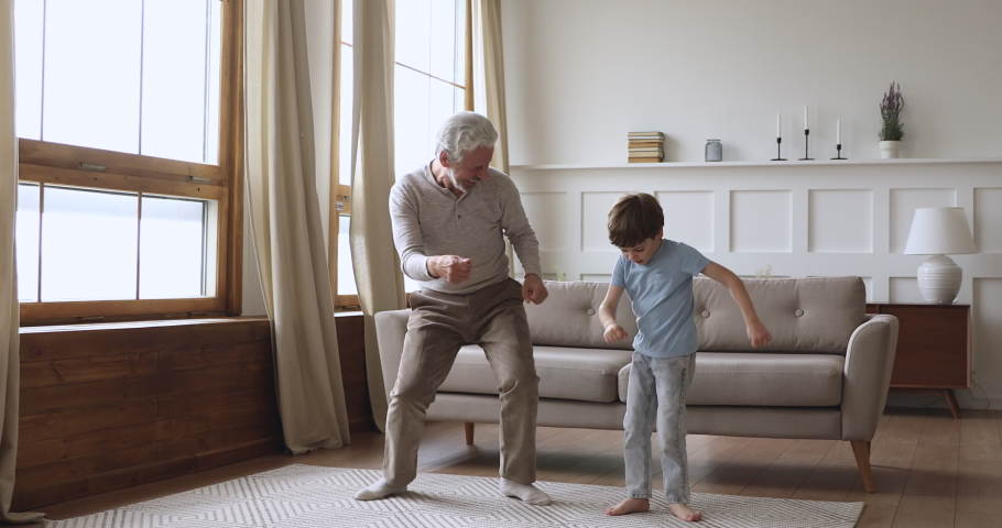 Happy two age generations active family dancing in living room, carefree old senior adult grandfather and cute preschool grandson having fun listening music jumping enjoying time together at home