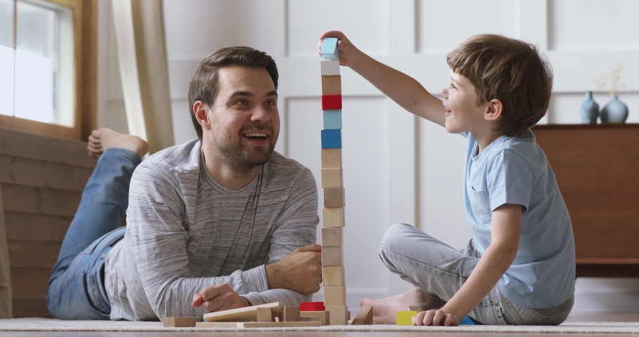 Happy adult parent dad helping cute preschool child son playing toys together on floor, caring father and little kid boy having fun laugh building constructor tower of colorful wooden blocks at home